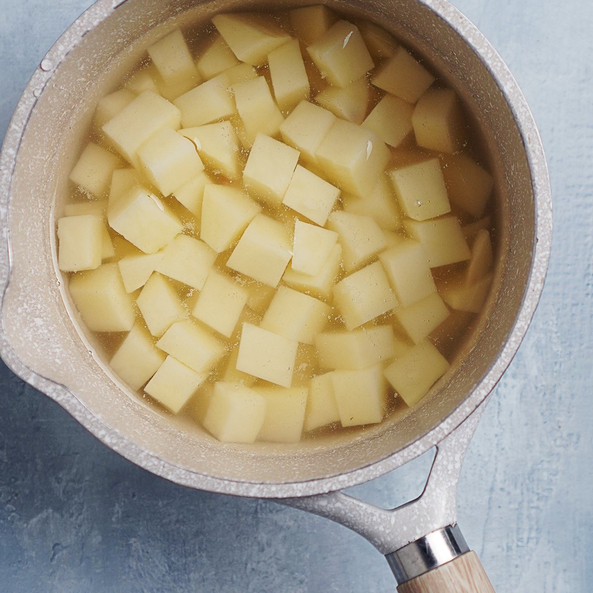 Cubed potatoes in a small saucepan with water.