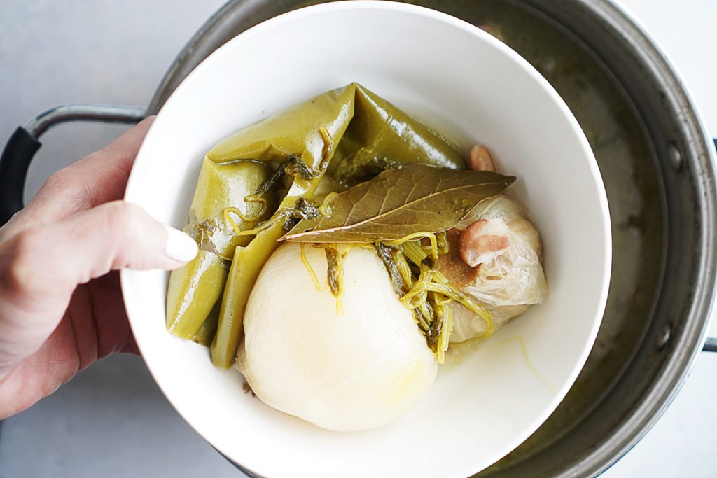 Removing from a pot cooked onion, chile, garlic and bay leaf and put on a plate