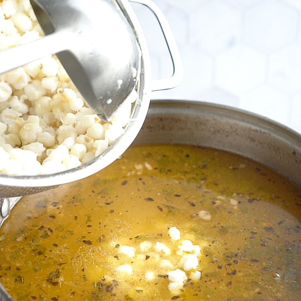 Adding hominy into a large pot with broth