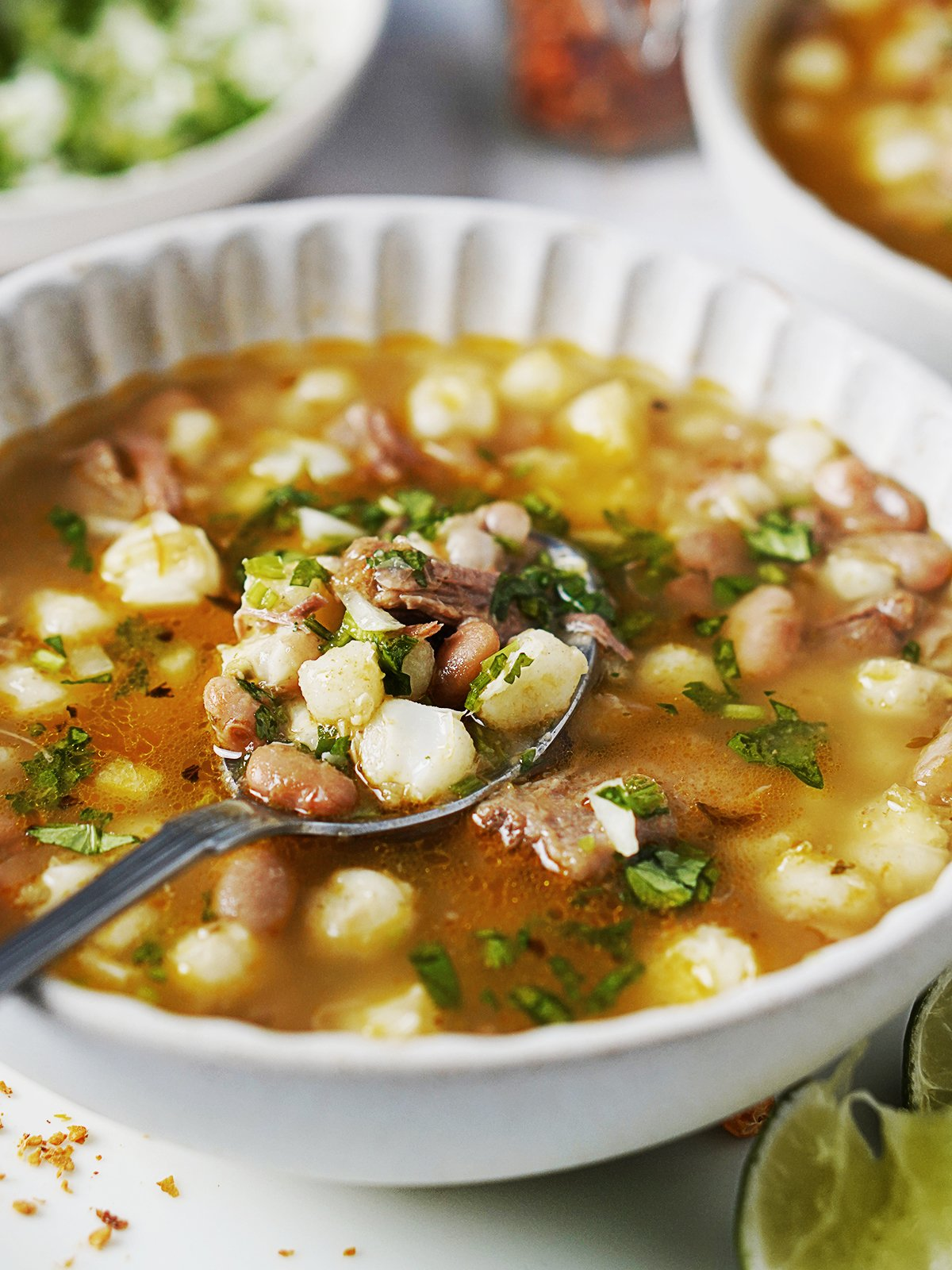 A white bowl with hominy and bean soup