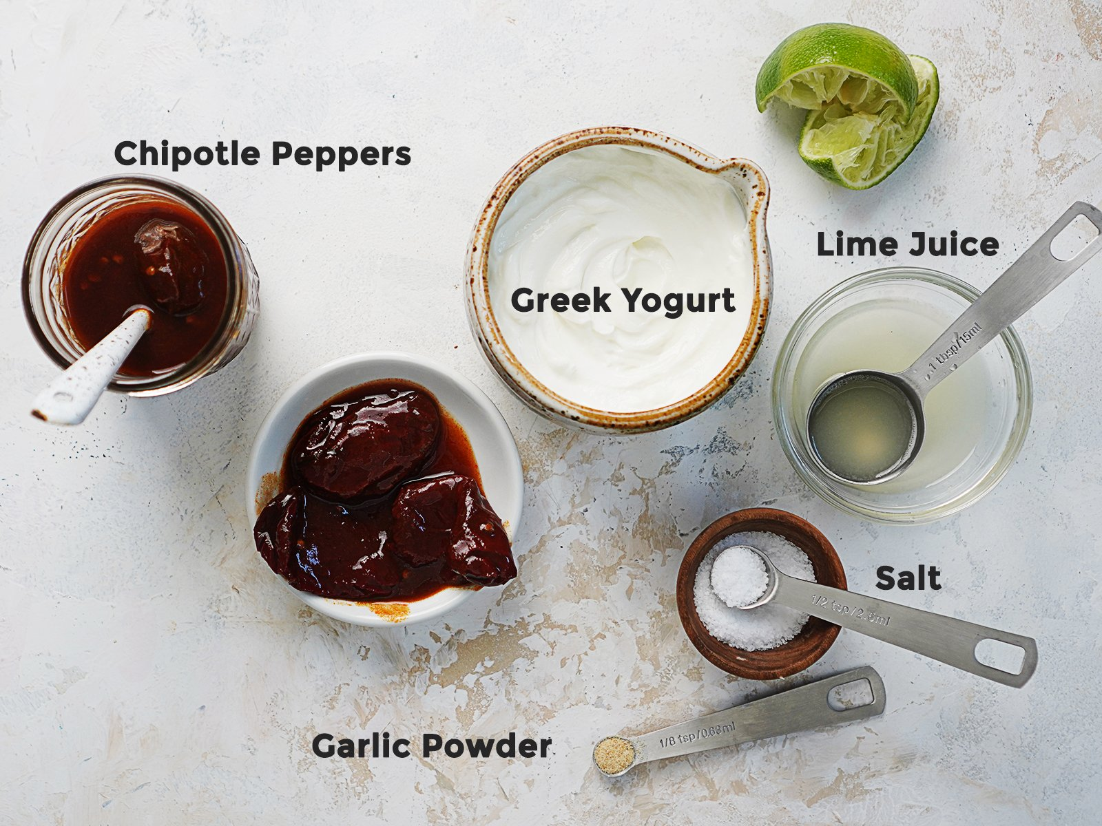 Ingredients in small bowls: chipotle peppers, Greek yogurt, lime juice, garlic powder and salt.