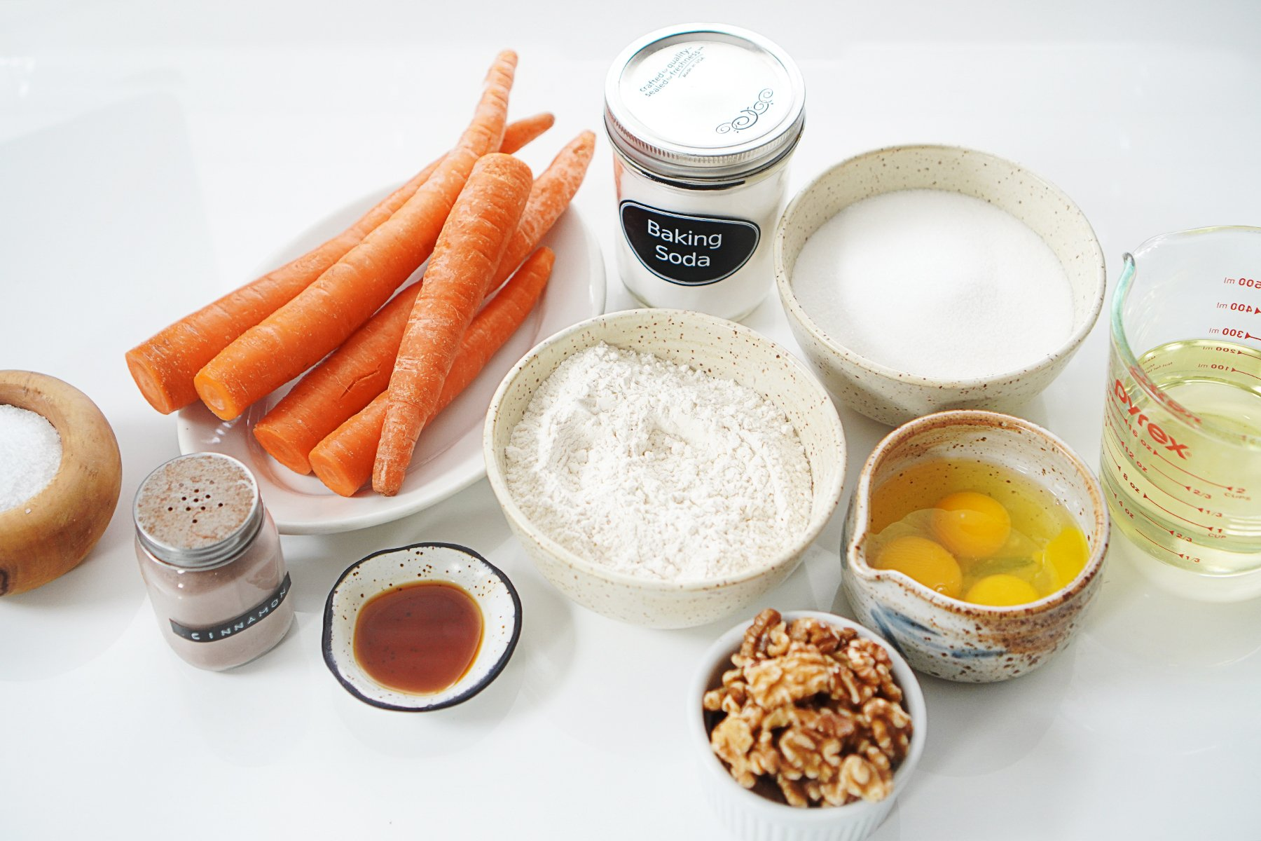 Ingredients on a white table: whole carrots, flour, sugar, eggs, oil, walnuts, cinnamon and vanilla