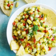 A pretty white bowl with Salsa De Piña and tortilla chips on the background