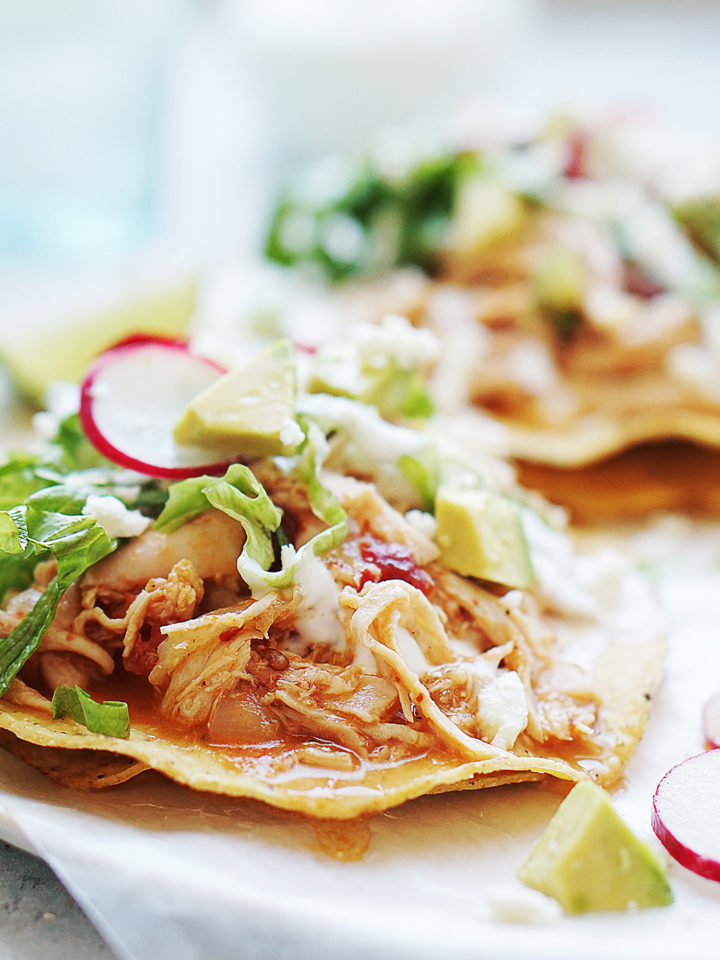 A tostada topped with Chicken Tinga, lettuce, radishes and avocado