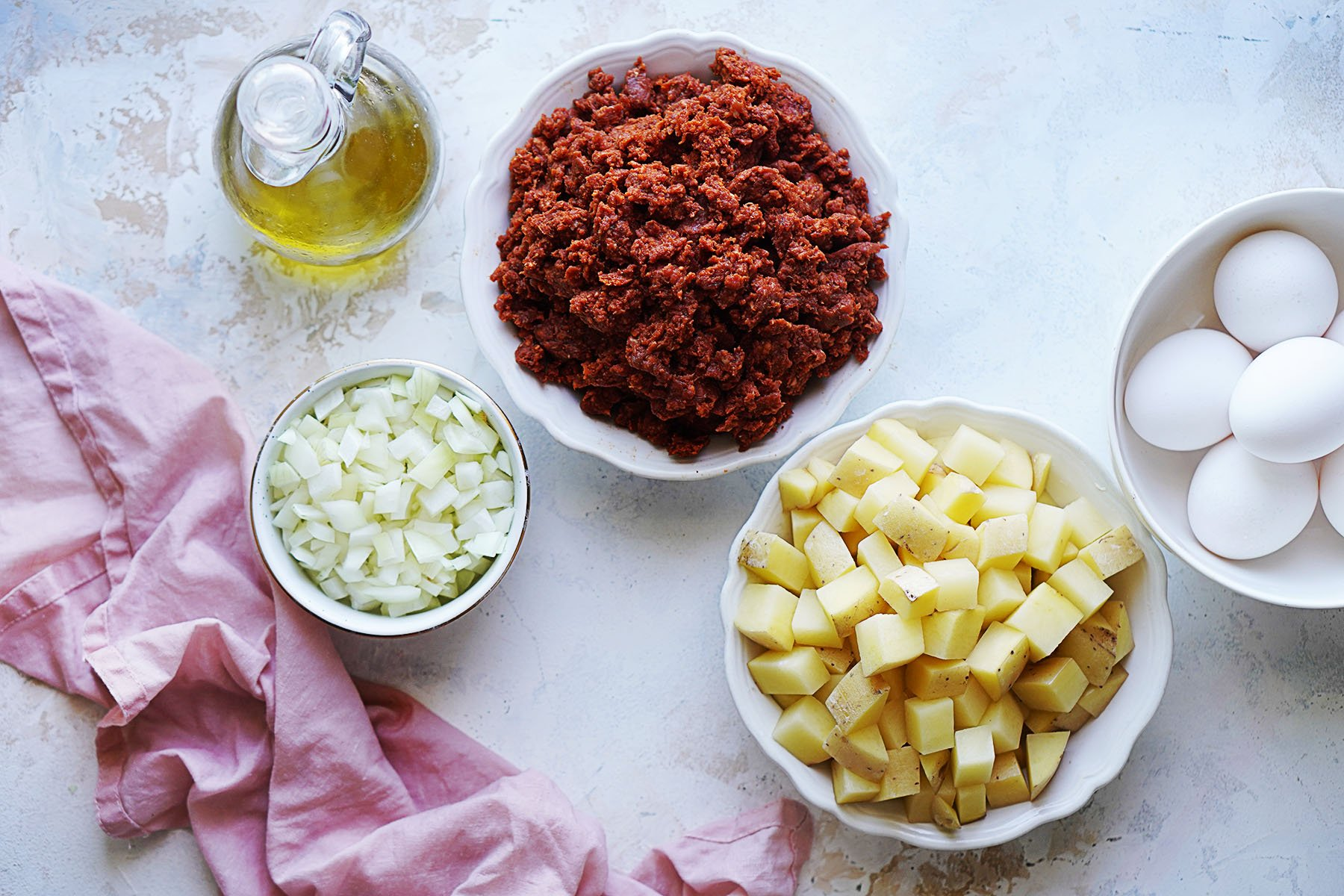 Ingredients placed in small bowls: cube potatoes, onions, ground beef chorizo, whole eggs and oil in a bottle