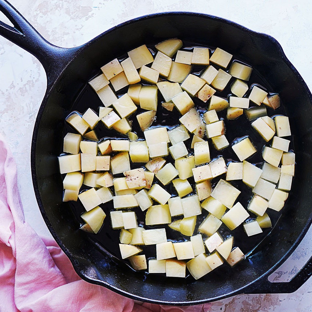 Raw cubed potatoes in a skillet