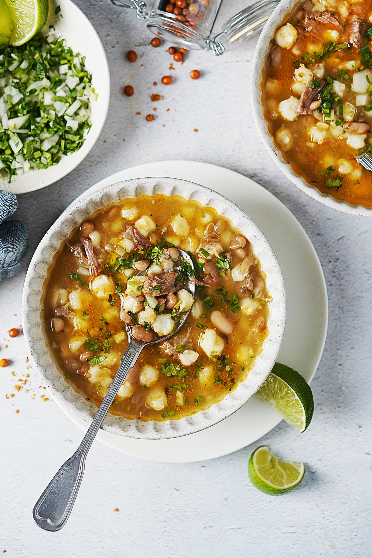 Two bowls of Soup with a spoon grabbing some soup.