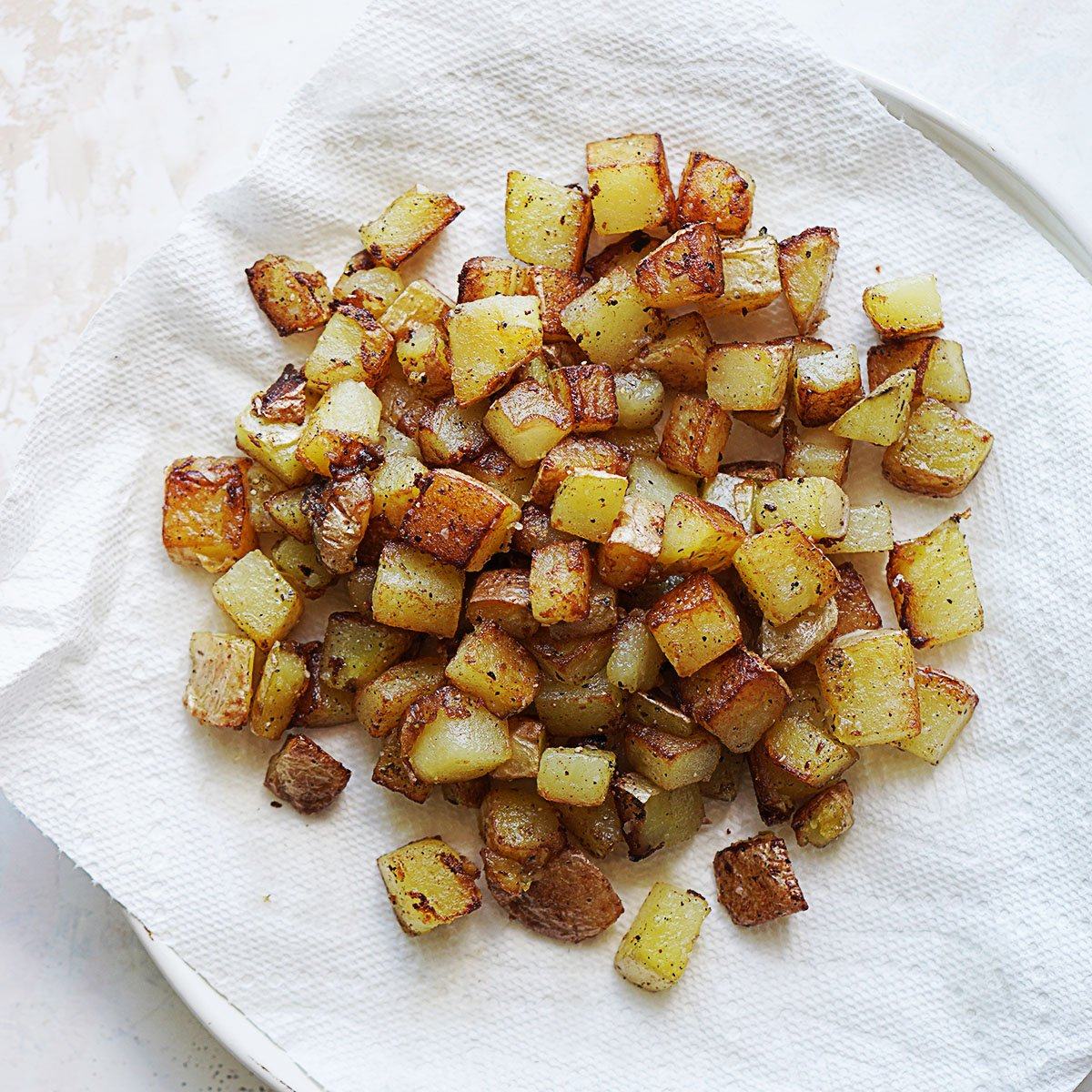 Fried cubed potatoes on a white plate on top of a paper towel