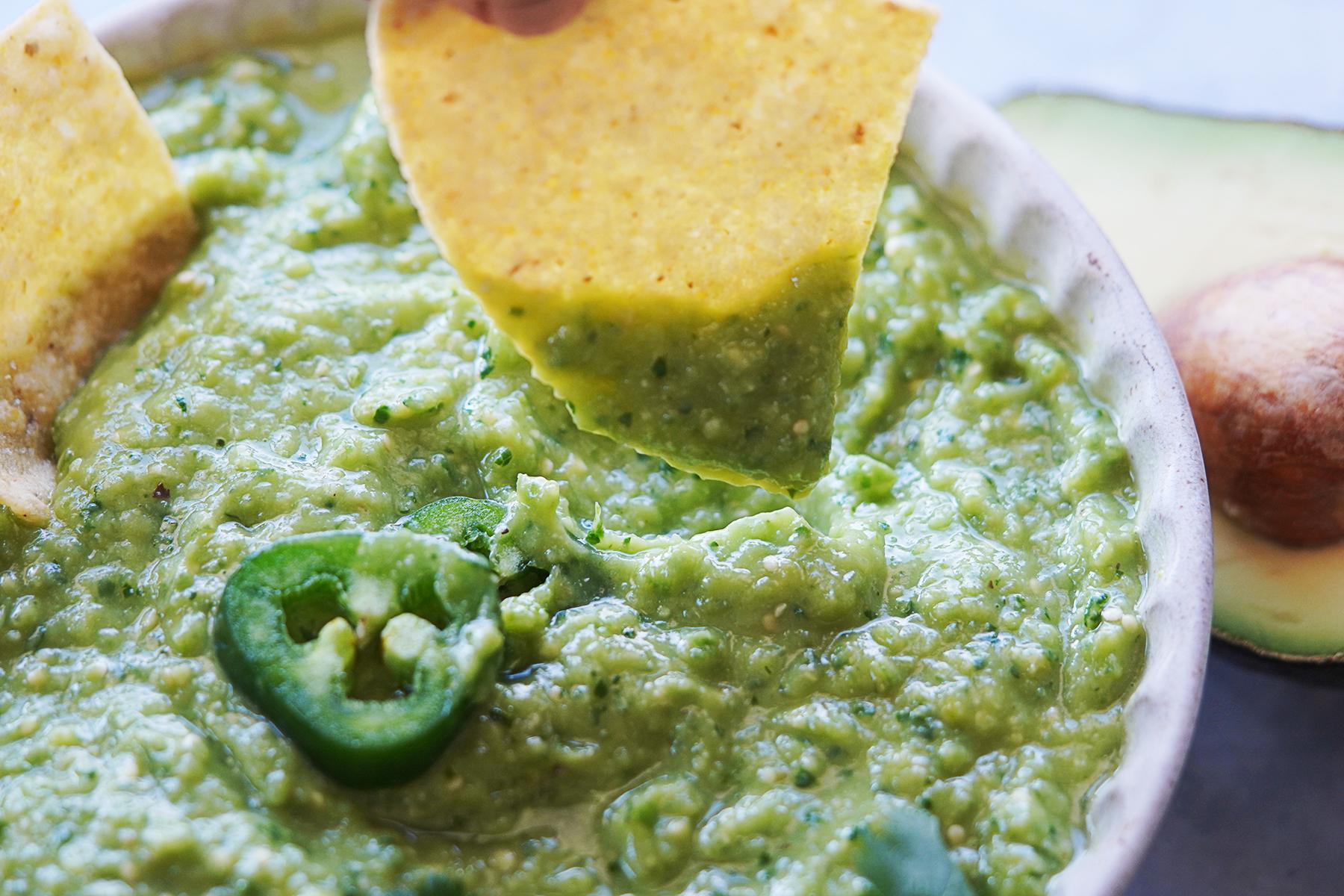 A tortilla chip dipping into Salsa De Aguacate