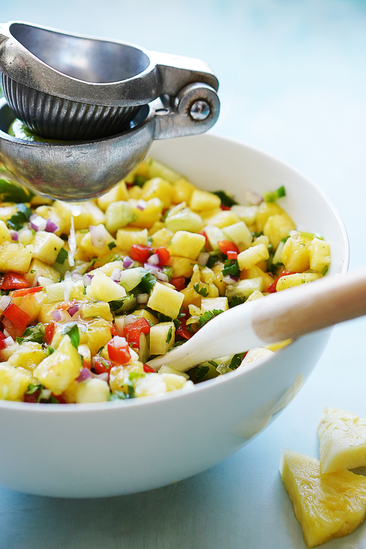 Squeezing lime over pineapple salsa