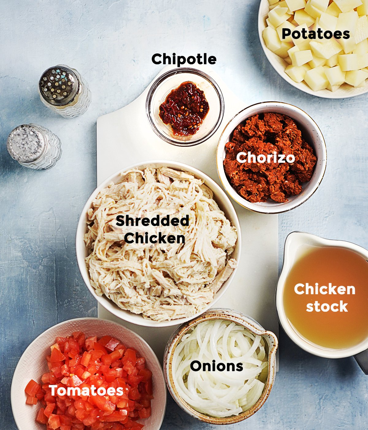 Ingredients in small bowls: shredded chicken, chorizo, onions, tomatoes, chipotle pepper and cubed potatoes