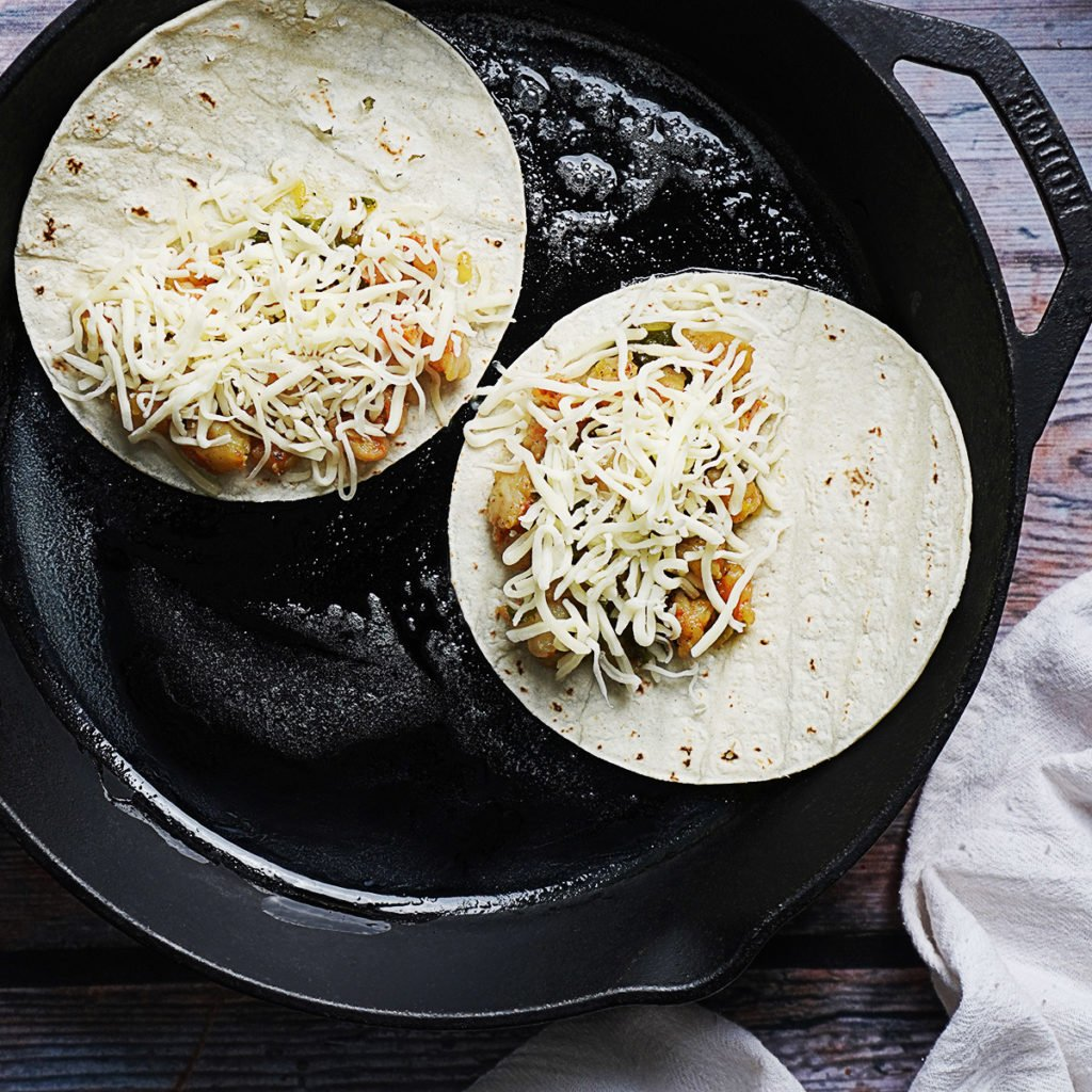 A skillet with two open tacos filled with shrimp and shredded cheese