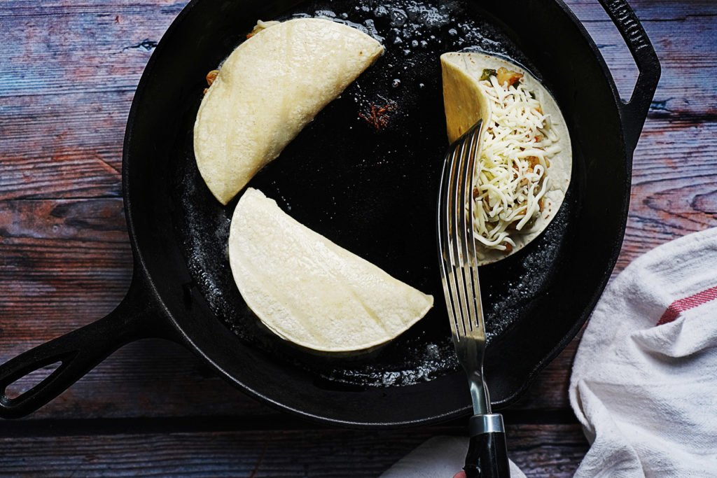 An iron skillet with 3 corn tortillas tacos. One is being flipped with a metal spatula