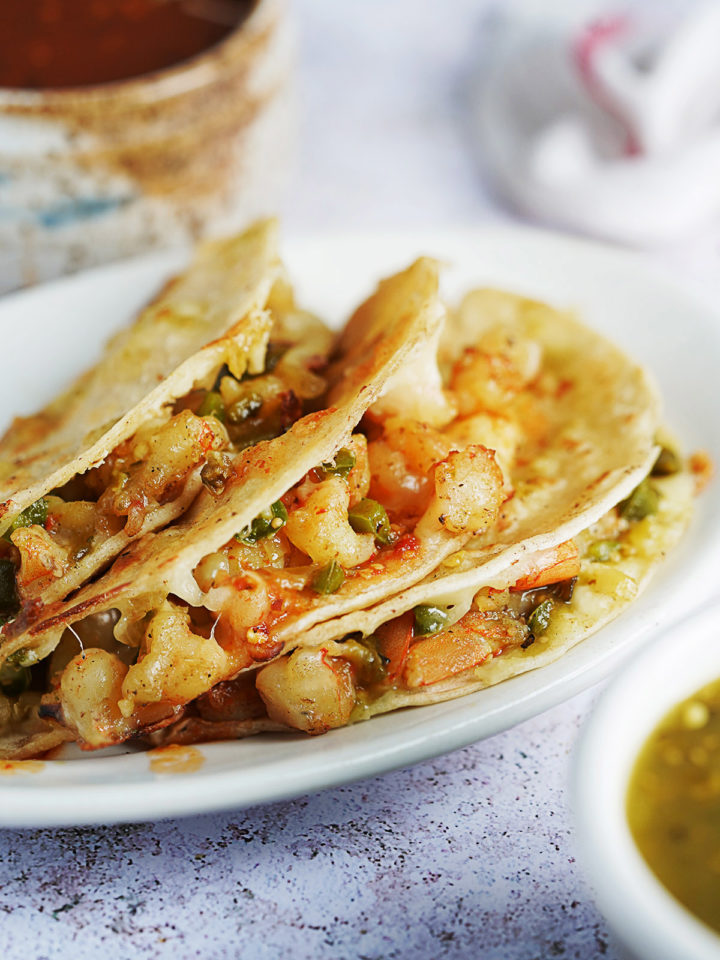 three tacos with shrimp and salsas on the side