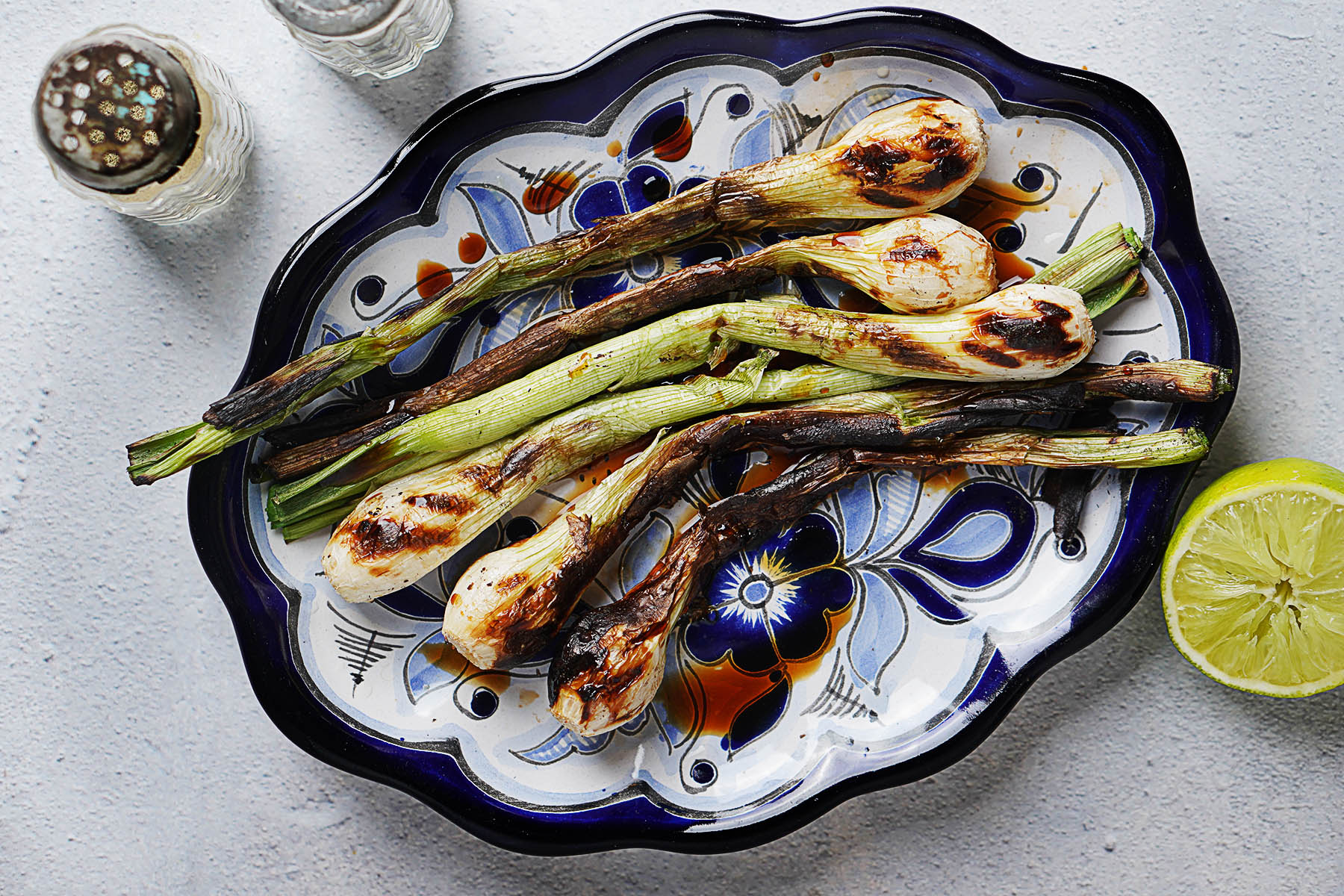 Cebollitas asadas on a blue plate with a lime on the side