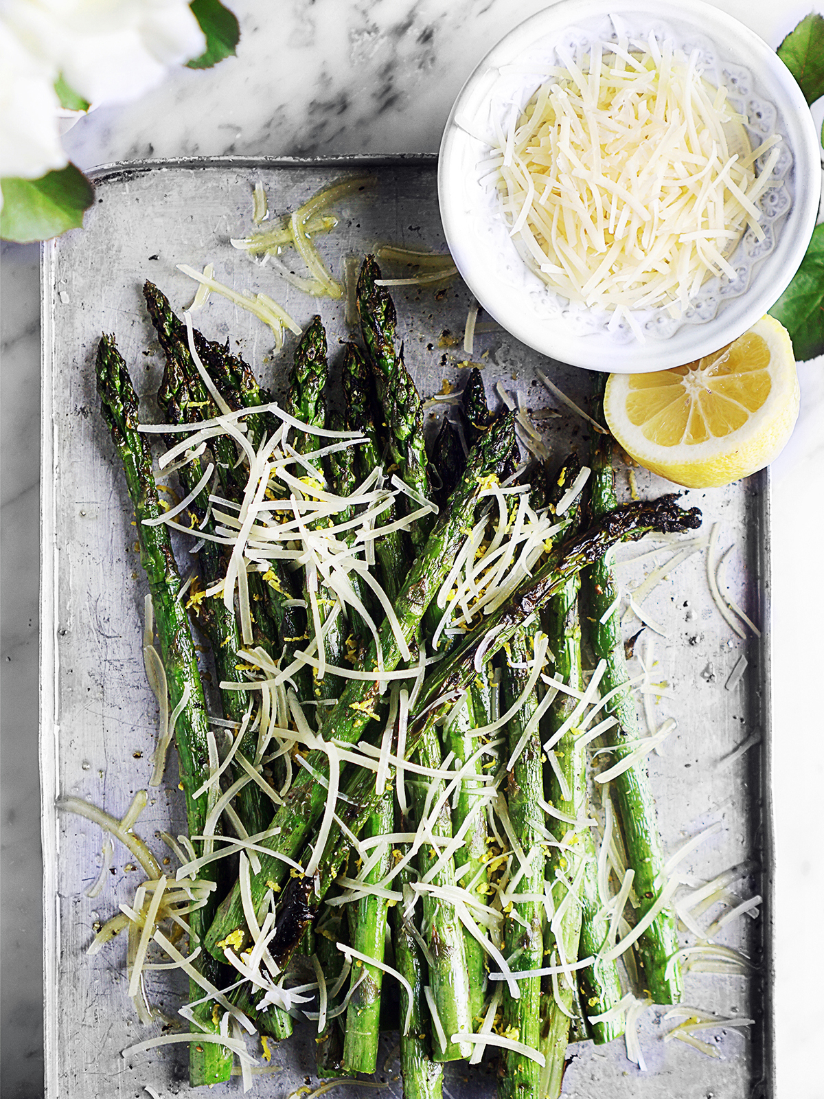 Esparragos asados on a metal baking tray with a small bowl of shredded parmesan