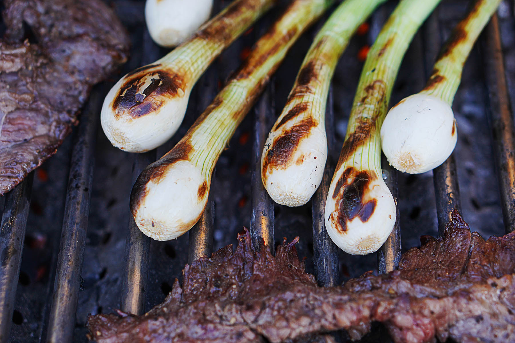 Green onions on a grill with carne asada on the side