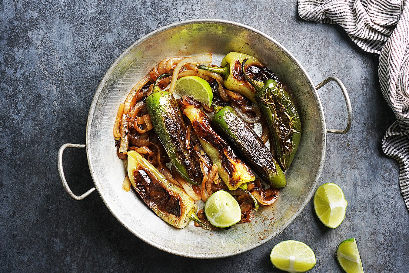 Blistered jalapeños, chile guerito peppers peppers and onions in a skillet