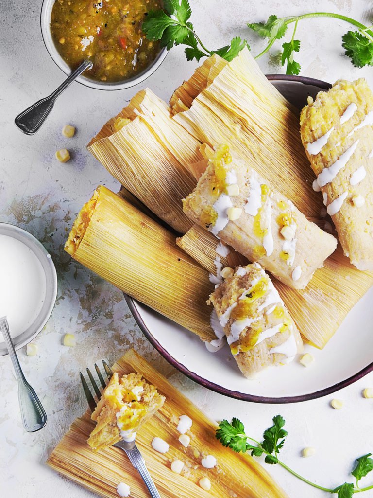 A large plate with corn tamales de elote still wrapped in husk