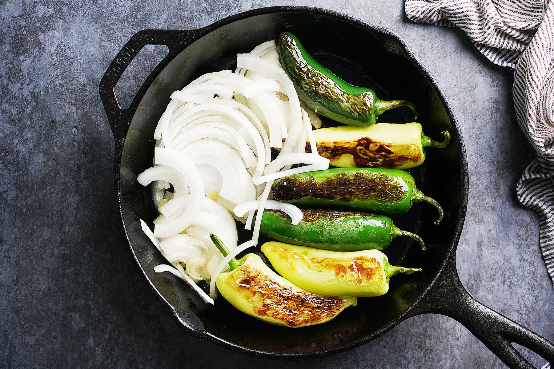 an iron skillet with fried jalapeños and raw onion slices