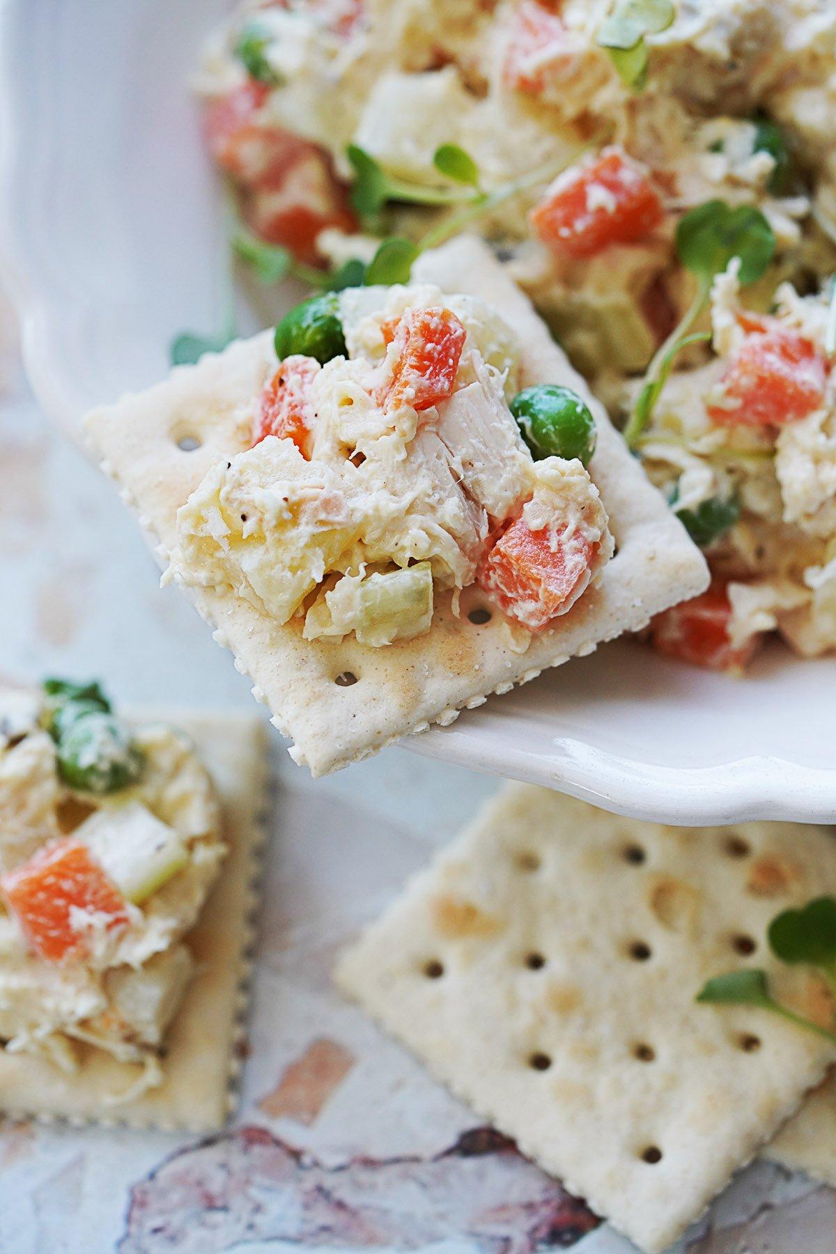 A saltine cracker topped with Ensalada De Pollo