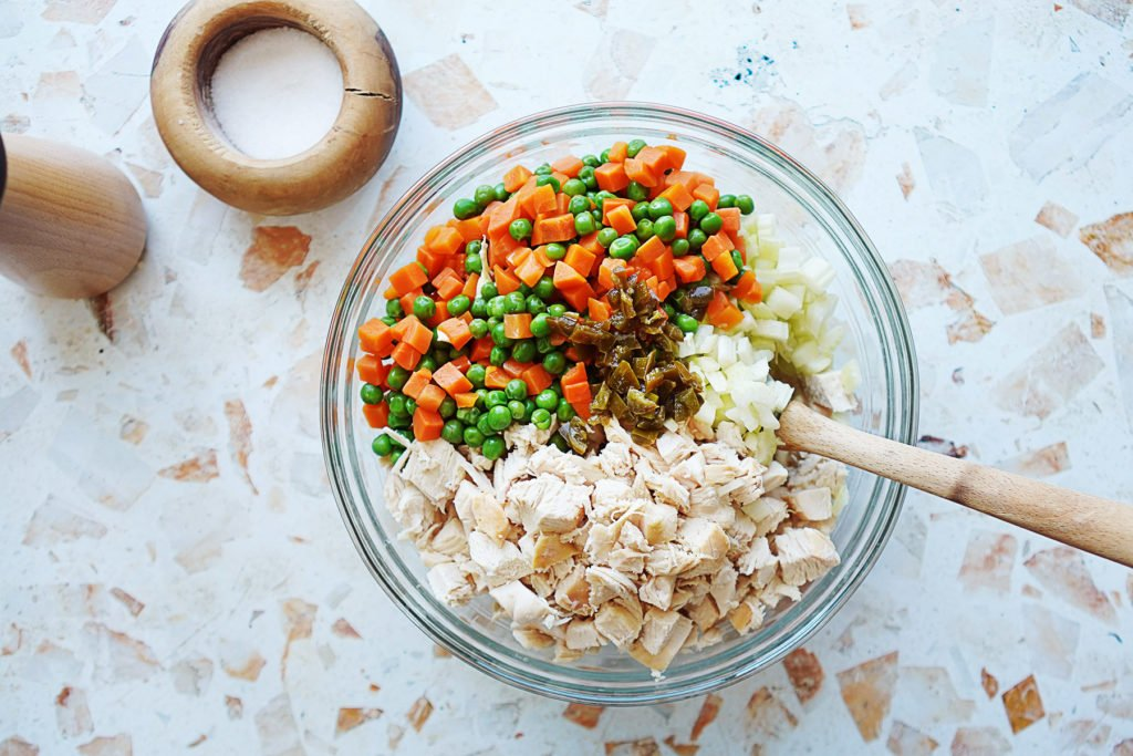 A bowl with cubed chicken, carrots & peas, and celery