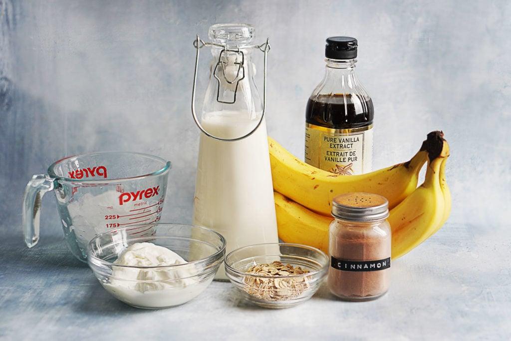 Ingredients for licuados on a blue background: milk, yogurt, oatmeal, cinnamon, bananas, vanilla extract