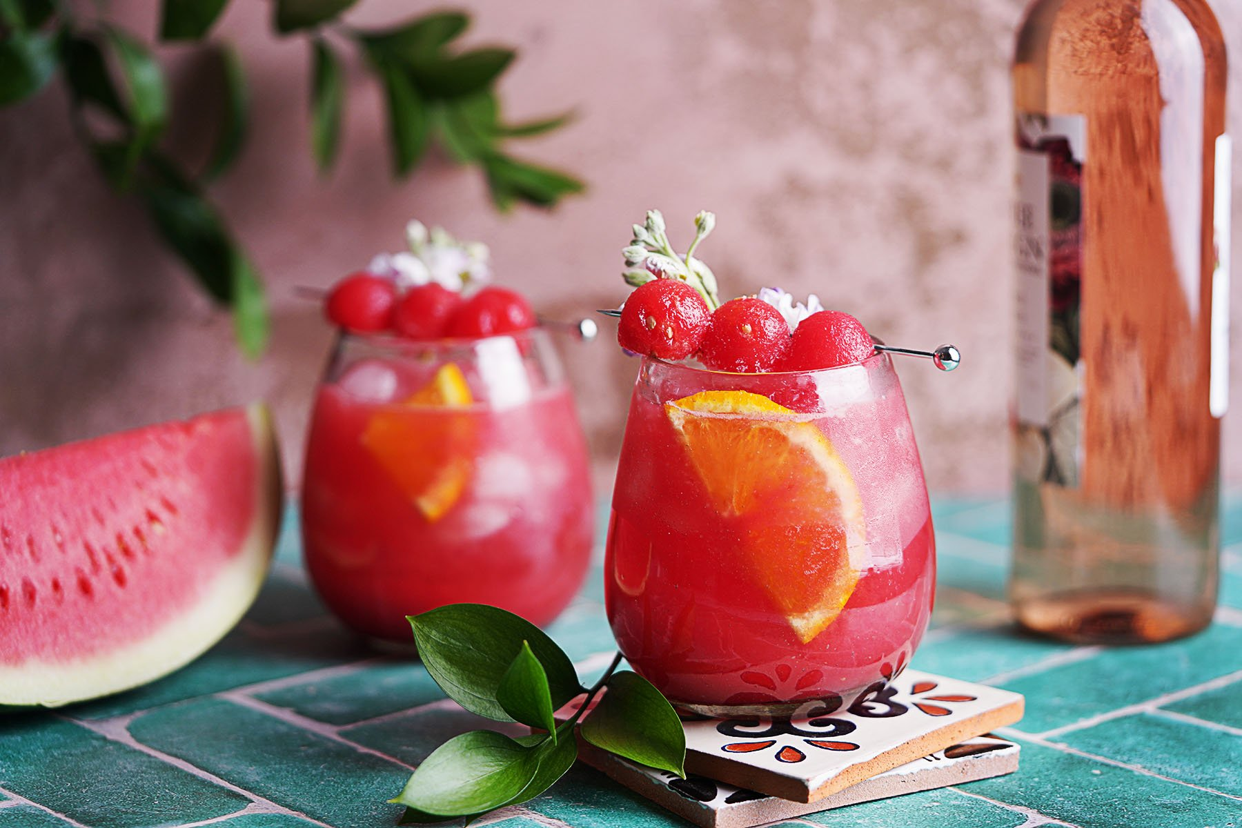 2 cocktail glasses with sangria on a green table
