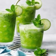 3 glasses with Agua De Pepino garnished with a slice of cucumber and mint