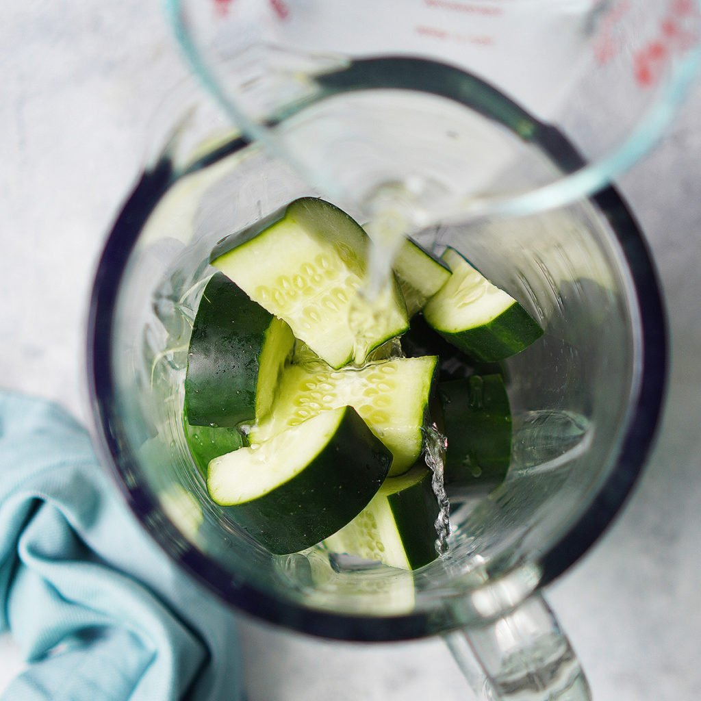 Cucumber slices in a blender glass with water being poured over it.