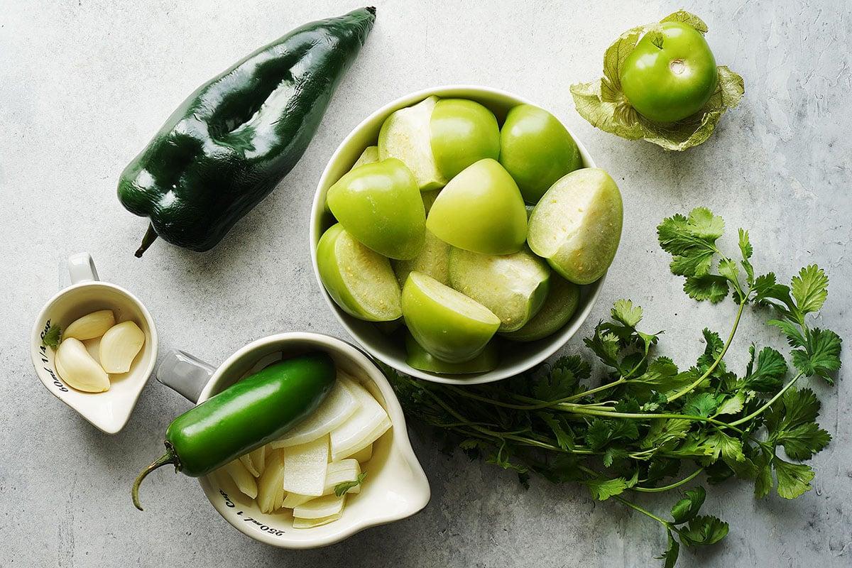 Salsa ingredients: tomatillos, jalapeño, onion, garlic, poblano pepper, and cilantro