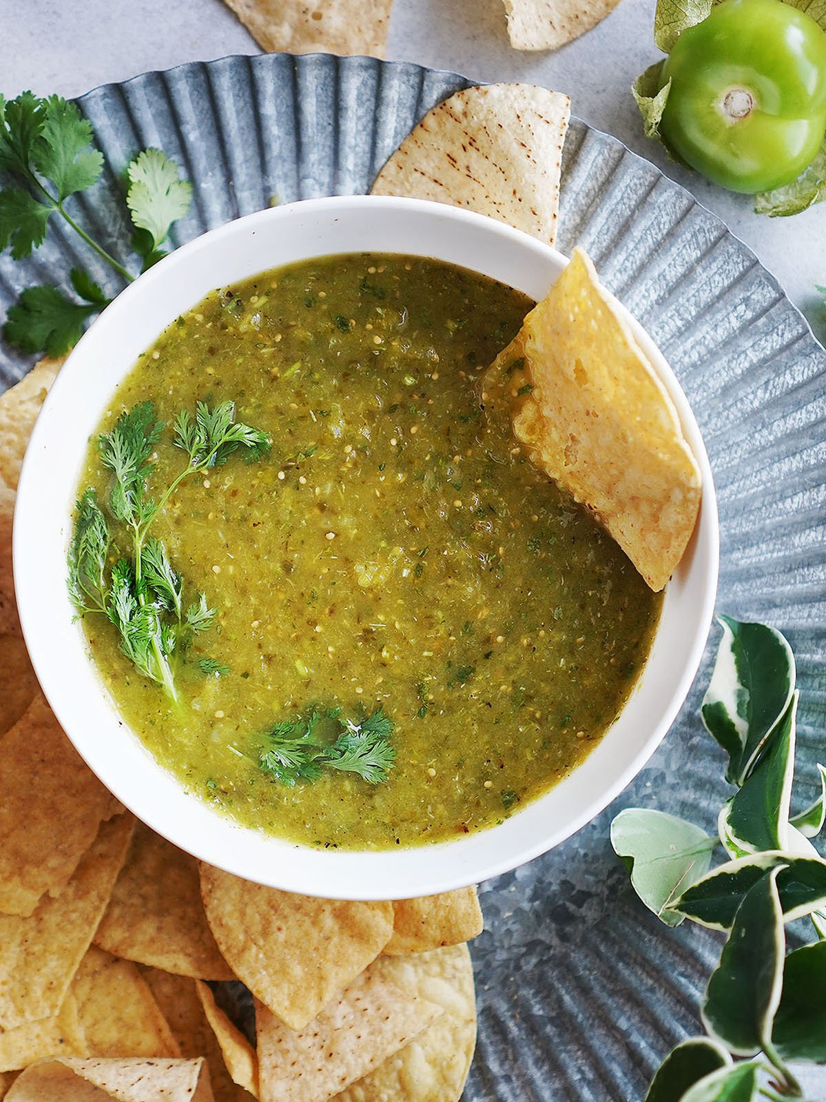 green salsa in a white bowl with tortilla chips on the side