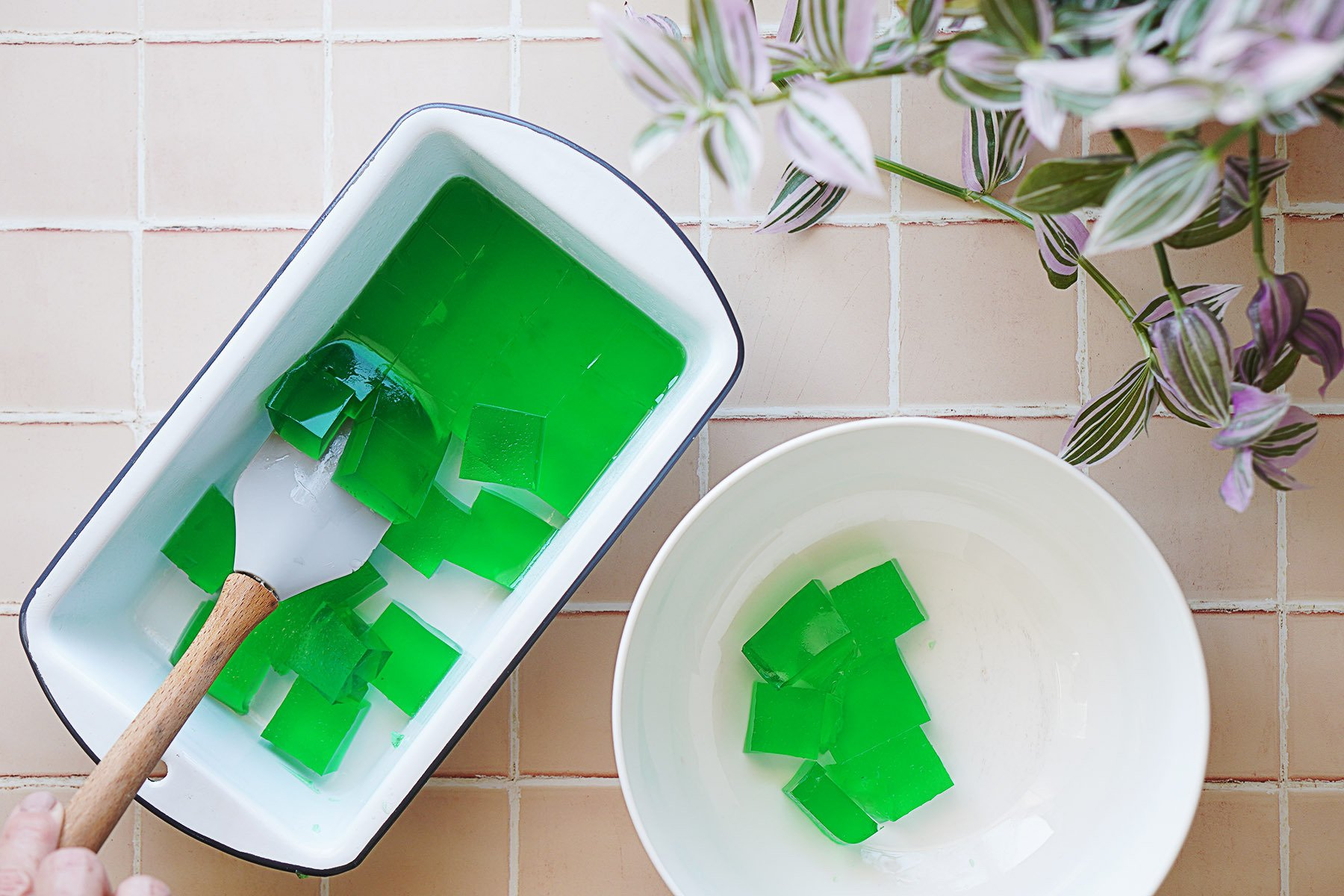 green jello in squares in a bread pan being removed with a spatula