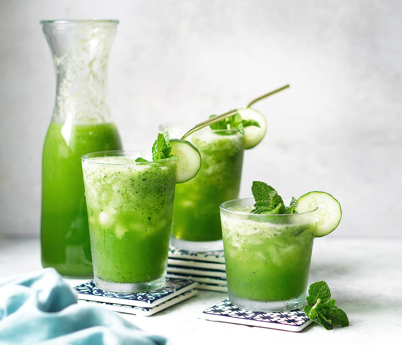 A jar with 3 glasses with Agua De Pepino garnished with a slice of cucumber and mint
