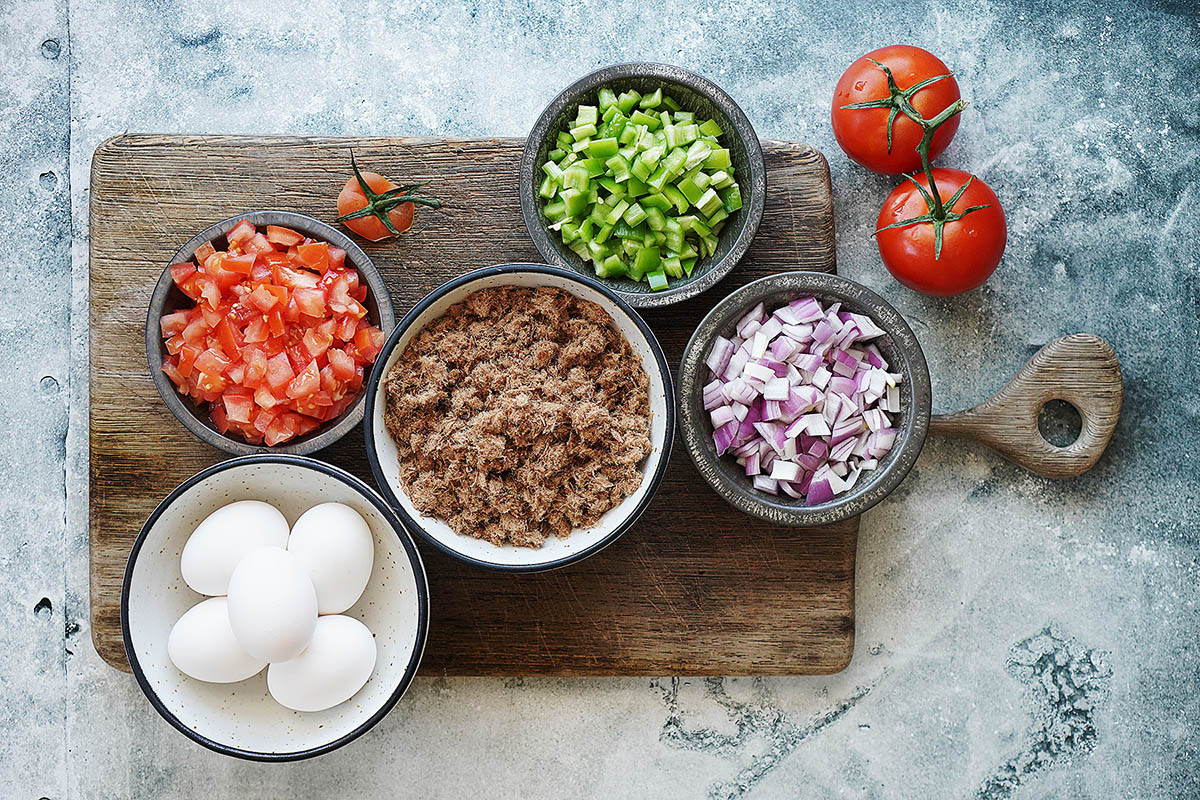 Ingredients in bowls: machaca, eggs, chopped red onions, chile verde and tomatoes