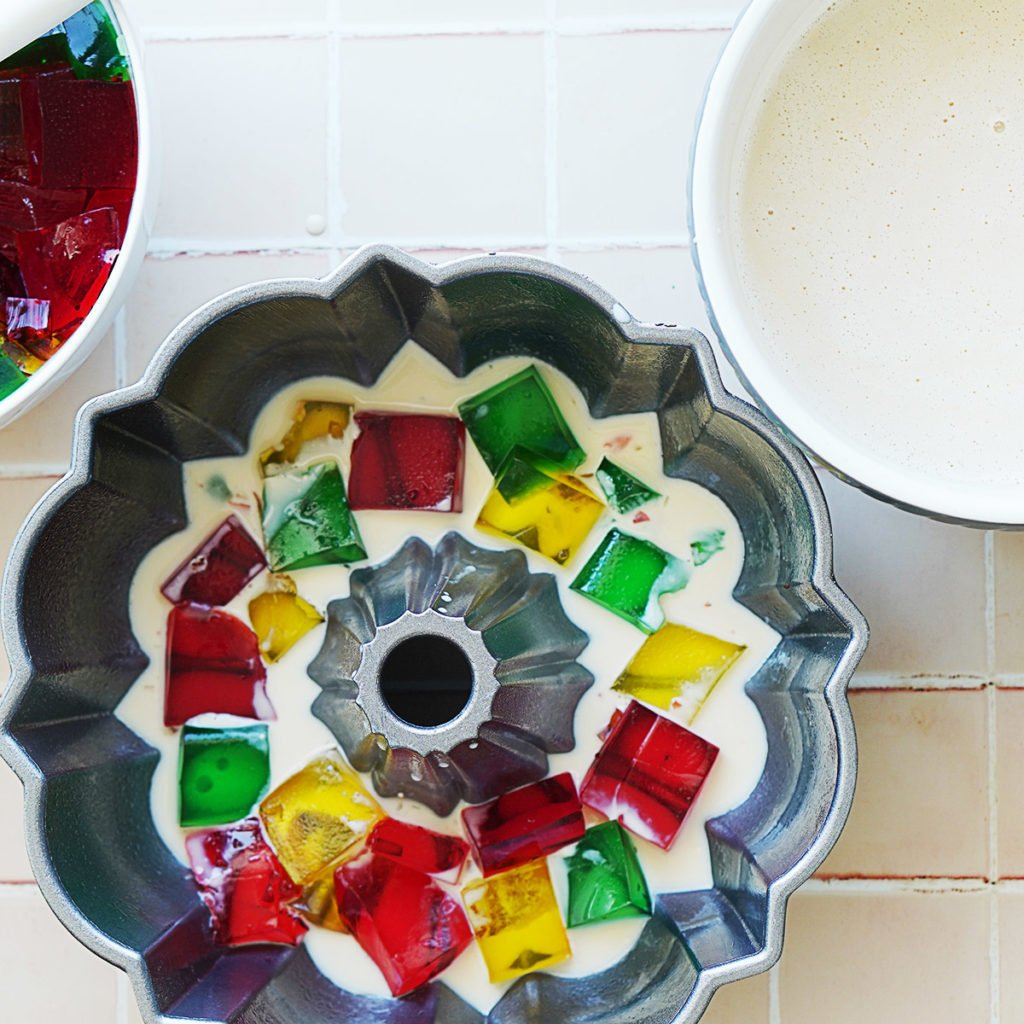 A bundt cake mold with jello squares and a milk mixture