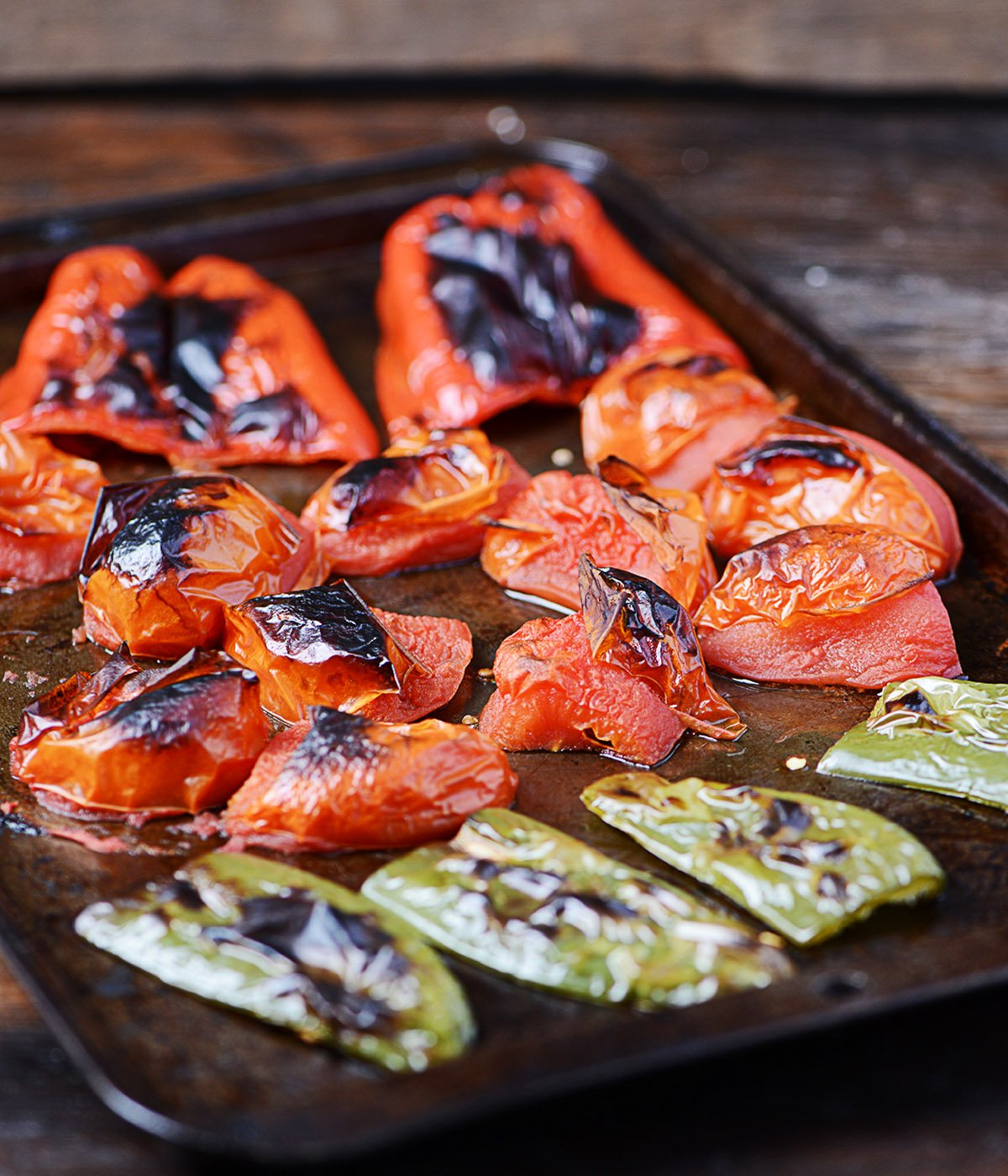 Charred broiled tomatos and jalapeños on a baking tray