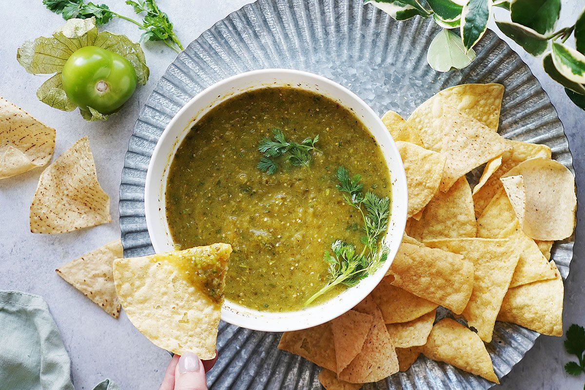 Tomatillo salsa verde on a gray platter with chips on the side