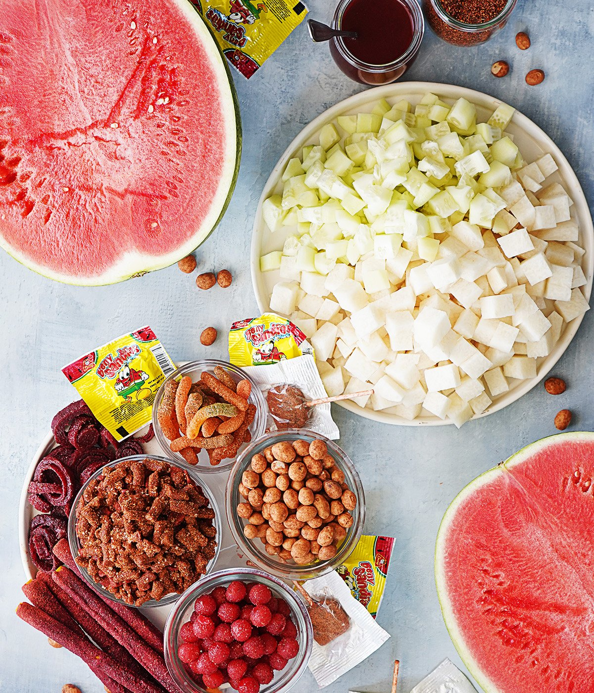 The candy & fruit toppings for Sandia Loca on a blue background.