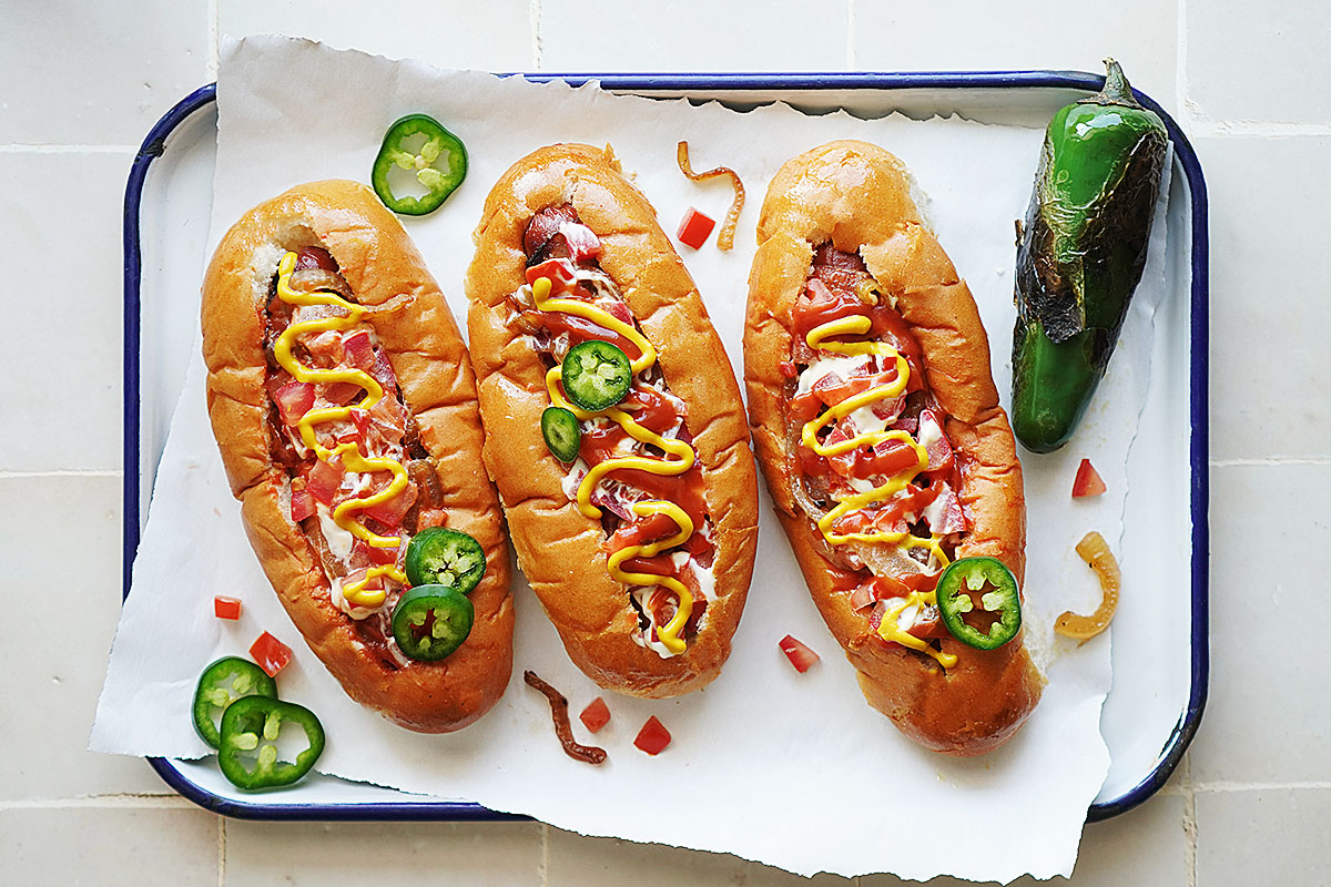 3 Sonoran Hot Dogs on a white tray with a roasted jalapeño on the side