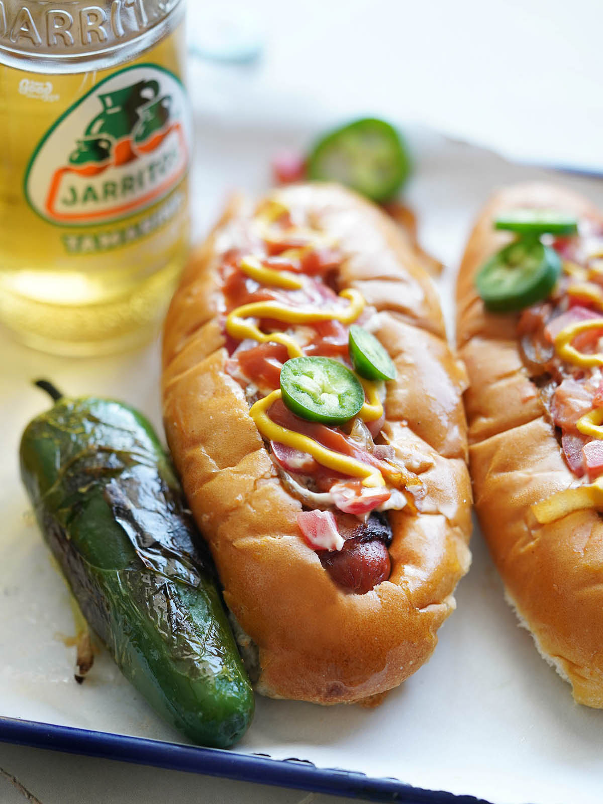 Two hot dogs with a roasted jalapeño on the side