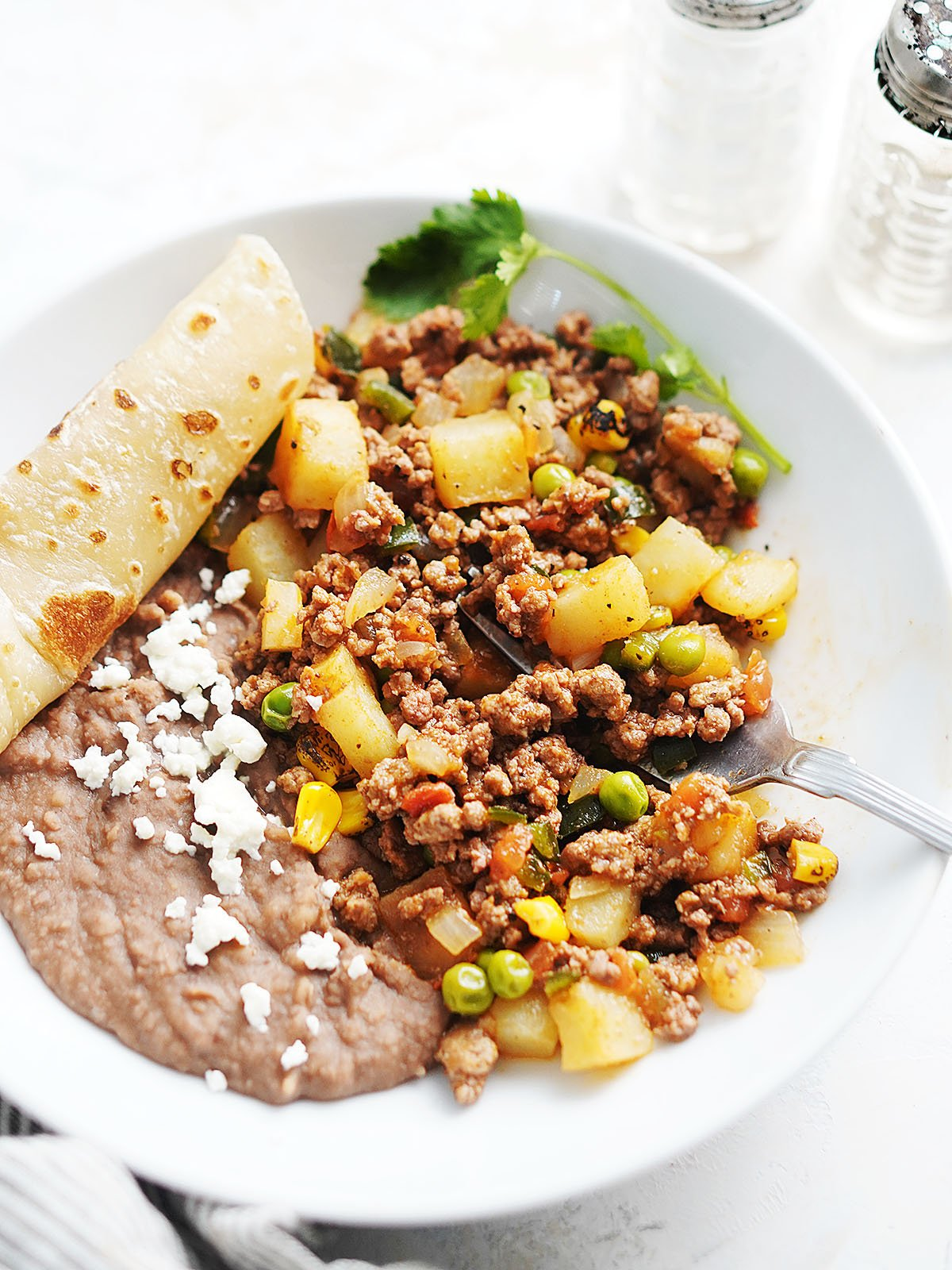 Ground beef and potatoes with beans on a white plate