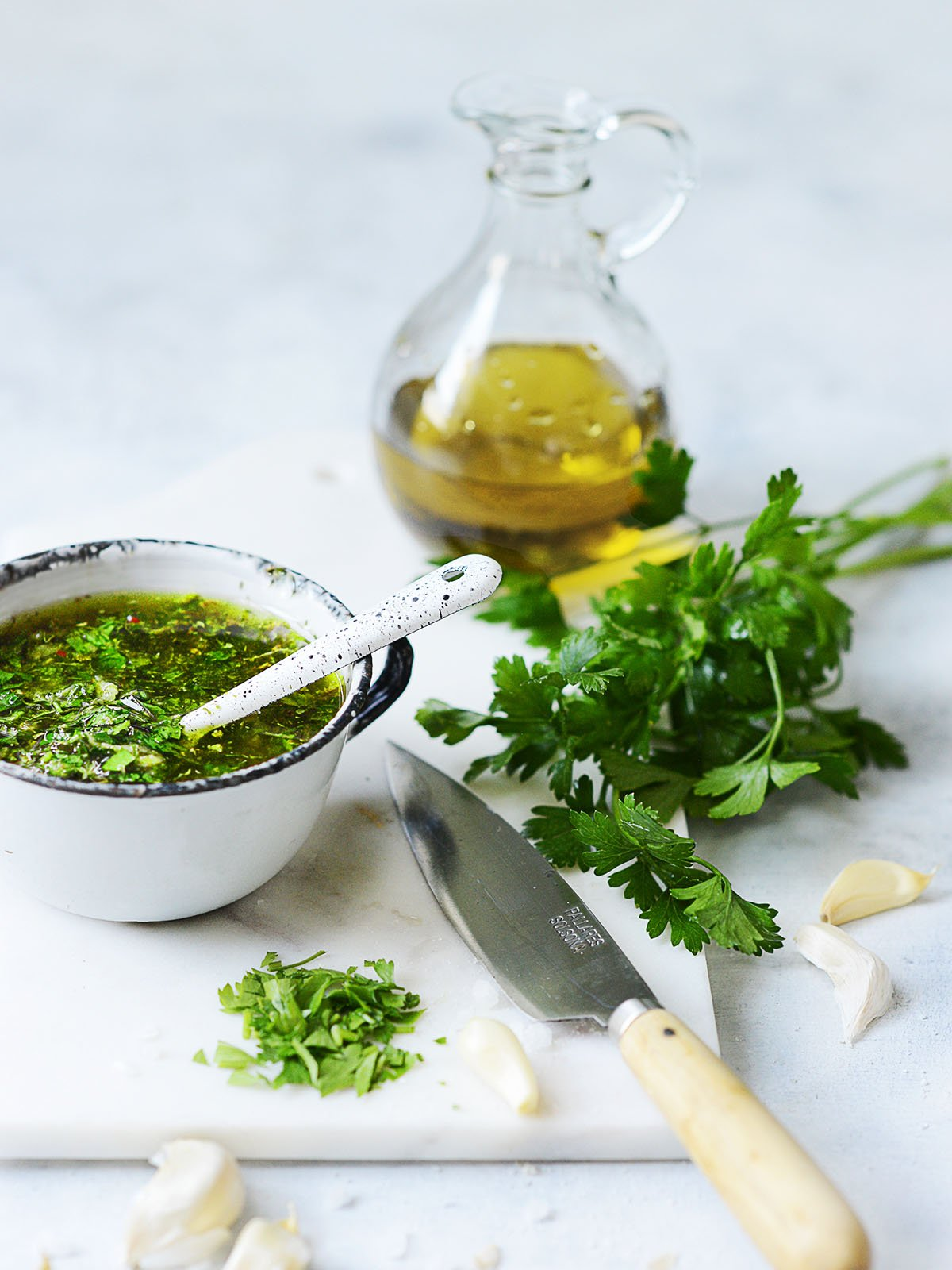 A cutting board with garlic, parsley, a knife and a cup with chimichurri
