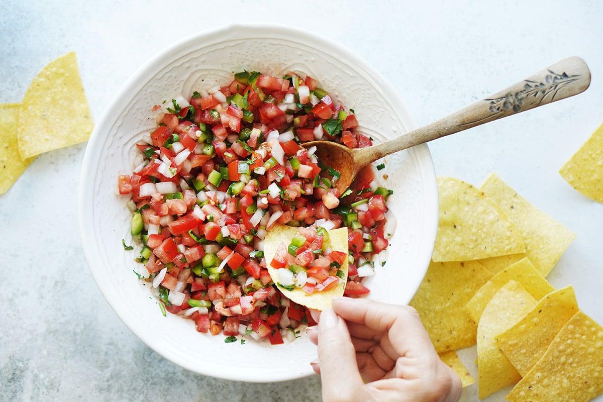 A hand holding a tortilla chip with salsa