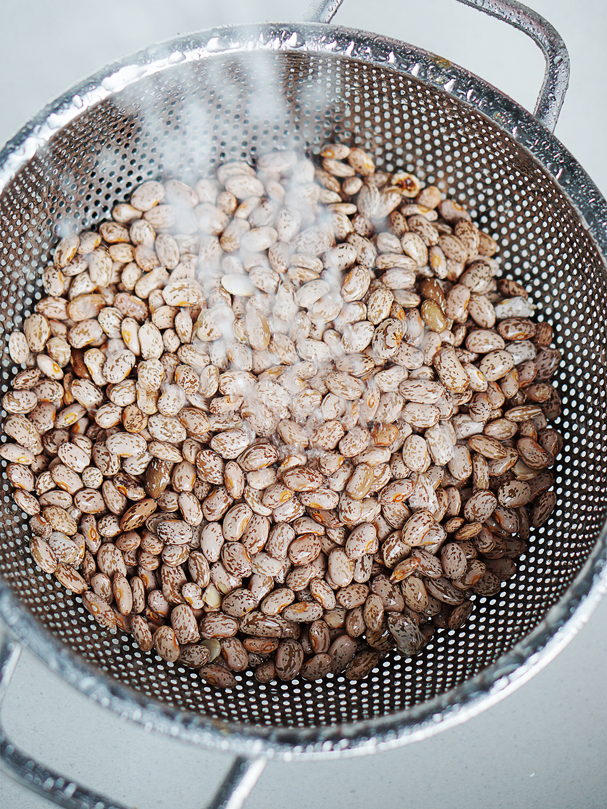 Rinsing pinto beans in a colander