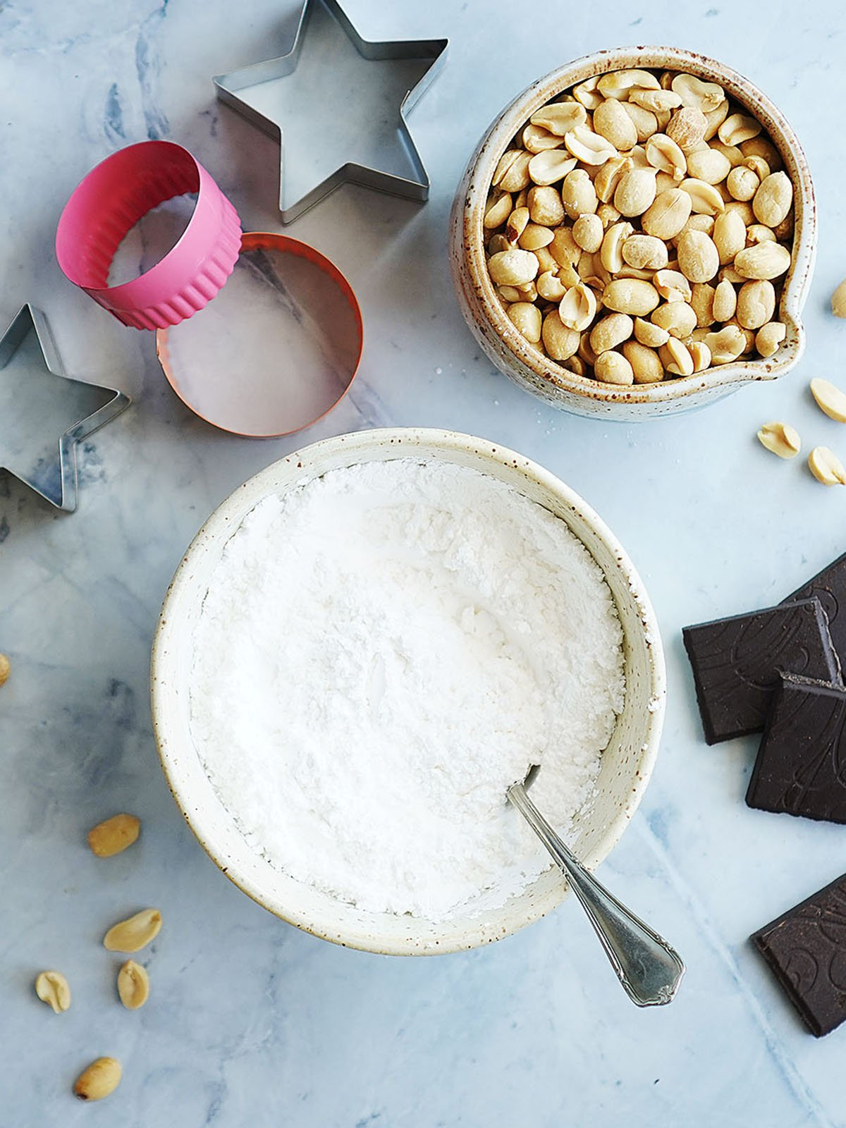 Ingredients on a blue background: peanuts (no shell) and powdered sugar on ceramic bowls