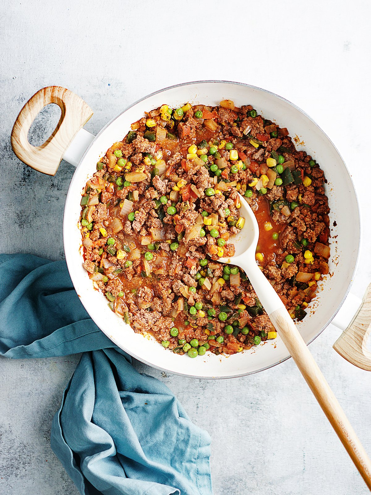 Large pan with picadillo on a blue board