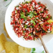 Pico De Gallo Salsa on a white bowl with tortilla chips on the side