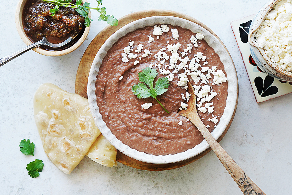Refried beans in a white bowl with a tortilla on the side