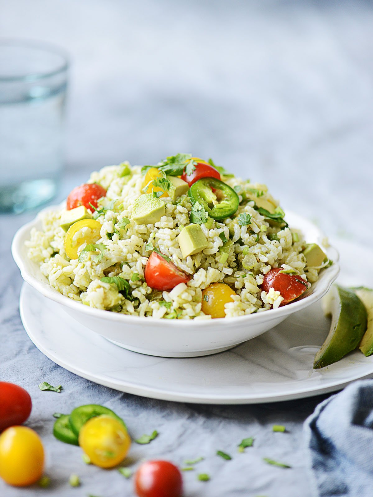 Green rice with tomatoes on a white bowl